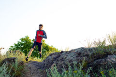 Young Sportsman Running on the Rocky Mountain Trai in the Evening. Active Lifestyle Royalty Free Stock Photos