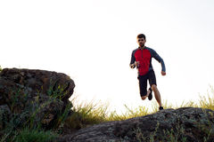 Young Sportsman Running on the Rocky Mountain Trai in the Evening. Active Lifestyle Royalty Free Stock Images