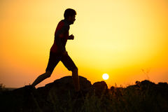 Young Sportsman Running on the Rocky Mountain Trail at Sunset. Active Lifestyle Royalty Free Stock Images