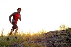 Young Sportsman Running on the Rocky Mountain Trail at Sunset. Active Lifestyle Royalty Free Stock Photo