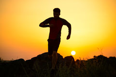 Young Sportsman Running on the Rocky Mountain Trail at Sunset. Active Lifestyle Stock Photography