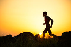 Young Sportsman Running on the Rocky Mountain Trail at Sunset. Active Lifestyle Stock Photos