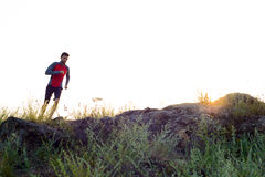 Young Sportsman Running on the Rocky Mountain Trail at Sunset. Active Lifestyle Royalty Free Stock Image
