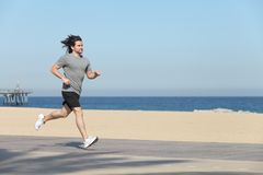 Young sportsman running on the seafront of the beach Royalty Free Stock Images