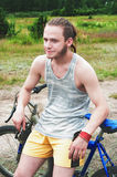 The young sportsman sits on a bicycle Stock Photography