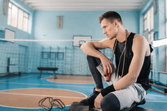 Young sportsman sitting with skipping rope on neck in sports hall Royalty Free Stock Photo
