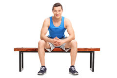 Young sportsman sitting on a wooden bench Stock Photo