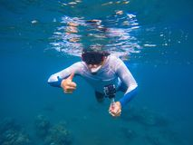 Young sportsman in snorkeling mask shows thumb underwater. Snorkel in tropical lagoon undersea photo. Summer holiday activity. Water sport in open sea Royalty Free Stock Images