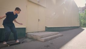 Young sportsman is spending leisure time skating outside. Boy is picking up speed and jumping over the barrier on stock video footage