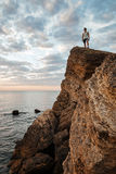 Young sportsman standing on the mountain rock by the sea Stock Images