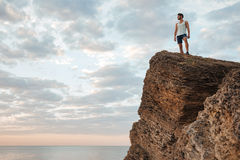 Young sportsman standing on the mountain rock by the sea Royalty Free Stock Photo
