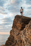Young sportsman standing on the mountain rock by the sea Stock Photos