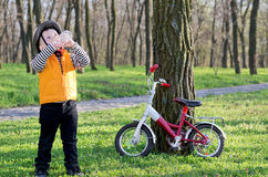 Young sportsman stopping for. Young boy dressed brightly coloured safety gear out riding his bicycle stopping for drink in  shade of  wooded park  quench his Royalty Free Stock Images