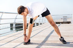 Young sportsman stretching legs during workout on pier. Handsome young sportsman stretching legs during workout on pier Royalty Free Stock Photos