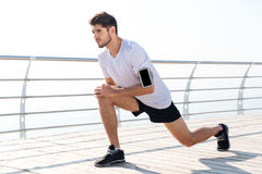 Young sportsman stretching legs during workout on pier. Handsome young sportsman stretching legs during workout on pier Stock Photo