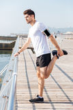 Young sportsman stretching legs during workout on pier. Handsome young sportsman stretching legs during workout on pier Royalty Free Stock Image