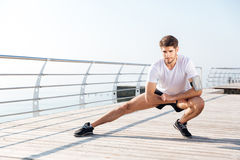 Young sportsman stretching legs during workout on pier. Handsome young sportsman stretching legs during workout on pier Stock Photography