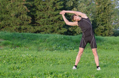 Young sportsman stretching. Before workout in park Stock Images