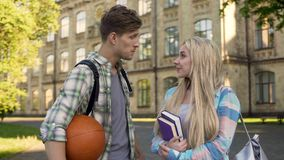 Young sportsman talking with beautiful blonde near college, asking for date. Stock photo stock photos