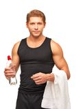 Young sportsman with towel and bottle of water. Handsome young sportsman with white towel and bottle of water taking rest after a workout. Dressed in black shirt Royalty Free Stock Images