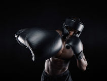 Young sportsman training boxing. Portrait of african male practicing boxing against black background. Male boxer throwing a punch in front. Young sportsman Royalty Free Stock Photo