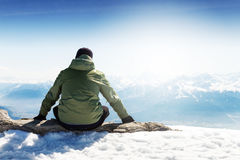 Young sportsman or traveler sitting on stone and looking on horizon. Mountain range on background. Beautiful Landscape. Horizontal. Travel Concept royalty free stock images