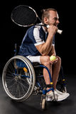 Young sportsman in wheelchair holding tennis racquet with ball and looking away Stock Photos