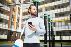 Young sportsman at workout area. Content determined young sportsman with red beard standing at workout area and using modern smartphone while checking exercise royalty free stock photos