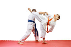 Young sportsmen in karategi are doing paired exercises Royalty Free Stock Photography