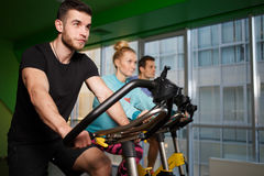 Young sportsmens on stationary bike Royalty Free Stock Image