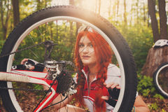 Young sportswoman bicyclist repairing her mtb bike in the forest Royalty Free Stock Photo