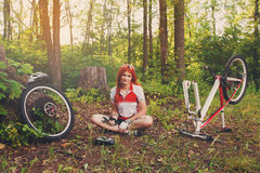 Young sportswoman bicyclist repairing her mtb bike in the forest Royalty Free Stock Image