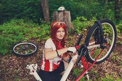 Young sportswoman bicyclist repairing her mtb bike in the forest Stock Photography