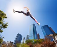 Determined fit girl jumping high in park stock photo