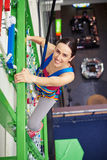 Young sportswoman in climbing high on the wall Stock Photo