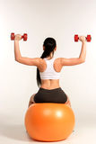 Young sportswoman doing fitness exercise with dumbbells on pilat Royalty Free Stock Images