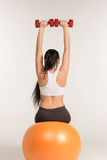 Young sportswoman doing fitness exercise with dumbbells on pilates ball Stock Photography