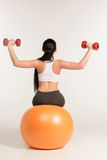 Young sportswoman doing fitness exercise with dumbbells on pilates ball Royalty Free Stock Photo