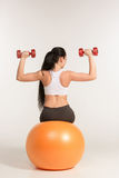 Young sportswoman doing fitness exercise with dumbbells on pilates ball Royalty Free Stock Photography