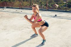 Young sportswoman doing squat exercise. On rooftop stock photo