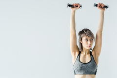 Young sportswoman exercising with dumbbells and looking away Stock Image
