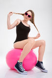 Young sportswoman having fun sitting on pink fitball Royalty Free Stock Image
