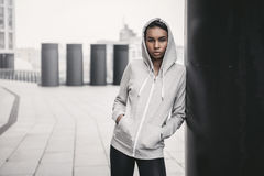 Young sportswoman in hood posing with hands in pockets and looking at camera Royalty Free Stock Photography