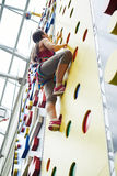 Young sportswoman in indoor rock-climbing center Stock Images