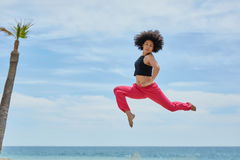 Young sportswoman jumping on beach with hands on waist Stock Photo