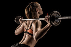 Young sportswoman lifting barbell isolated on black royalty free stock photo