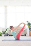 Young sportswoman meditating in boat pose on yoga mat Stock Image