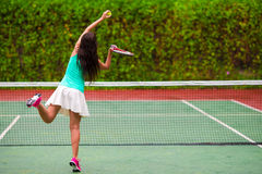 Young sportswoman playing tennis on tropical Stock Photos