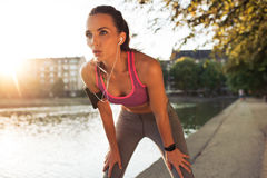 Young sportswoman resting after run. Female runner standing bent over and catching her breath after a running session along lake in city. Young sports woman Royalty Free Stock Photos