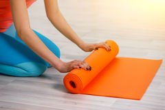 Young sportswoman rolling down mat Stock Photography